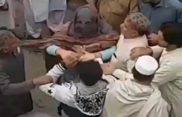 In the video footage, a woman can be seen furiously slapping and roughing up the two men.