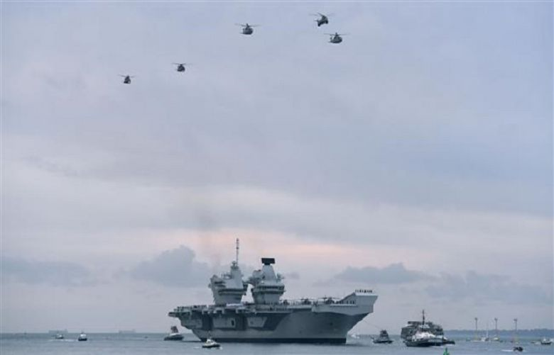 Wildcat and Merlin helicopters fly above the 65,000-tonne British aircraft carrier HMS Queen Elizabeth as tug boats maneuver it into Portsmouth Harbor in Portsmouth, southern England, August 16, 2017.