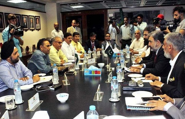 Pakistan's Commissioner for Indus Waters Syed Muhammad Mehar Ali Shah and members of his team talk to Indian Indus Water Commissioner Pradeep Kumar Saxena and other members of his delegation during a meeting in Lahore in August.