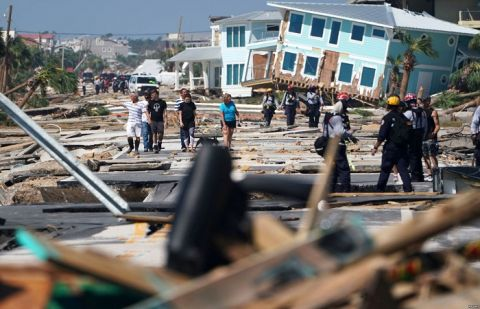 First responders and residents walk along a debris-littered street following Hurricane Michael, in Mexico Beach, Florida, Oct. 11, 2018.