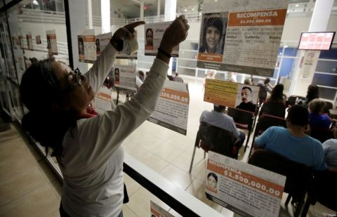 A woman attaches fliers with the photographs and details of missing persons to the glass windows of the attorney general's office, during World Day against Trafficking in Persons, in Ciudad Juarez, Mexico, July 30, 2018.