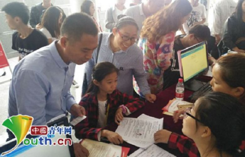 Accompanied by her parents, Zhang Yiwen registers at the registration desk at Shangqiu Institute of Technology, central China's Henan province, Sept. 10, 2017.