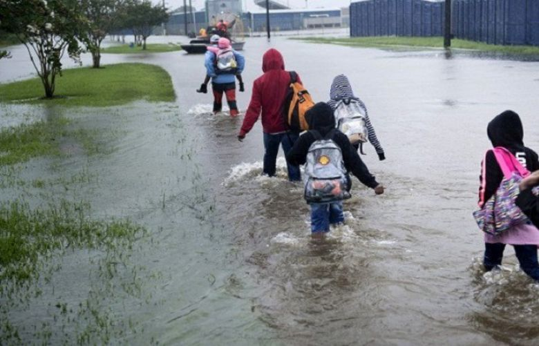 People walk to a Harris County Sherif air boat while escaping a flooded neighborhood during the aftermath of Hurricane Harvey on August 29, 2017 in Houston, Texas. Floodwaters have breached a levee south of the city of Houston, officials said Tuesday, urging residents to leave the area immediately.