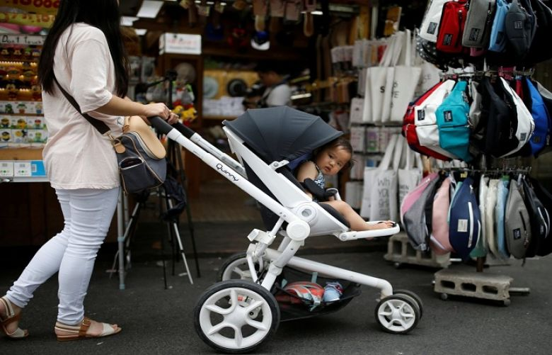 A woman pushing her baby in a stroller in the Hongdae area of Seoul, South Korea.