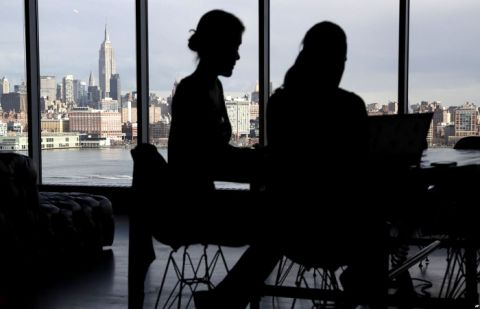 The New York City skyline is seen at a distance as two women are seen on their laptops in a building in Hoboken, New Jersey, Jan. 23, 2018. With privacy breaches on the rise, there is a growing push for greater online protection of consumers.