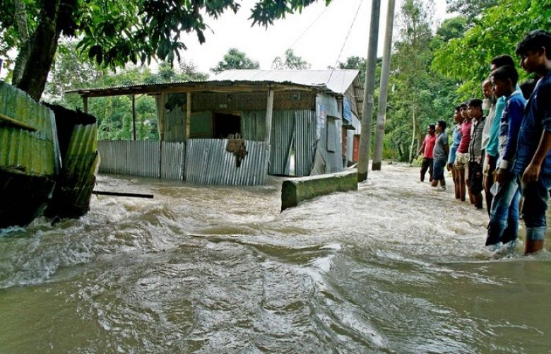 Bystanders look on as floodwaters rage near a house in Kurigram, northern Bangladesh on August 14.
