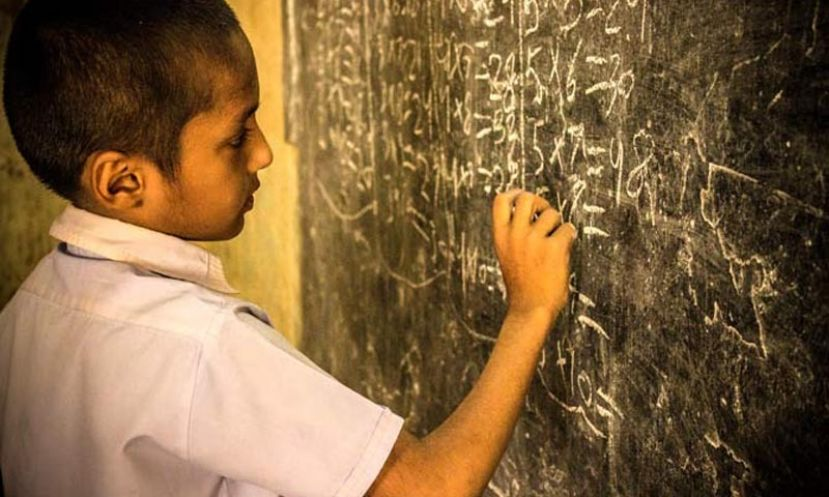 A boy practicing math on a blackboard during a lecture at Jufelhurst School in Karachi.