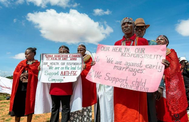 "Massai community members hold banners with messages, such as ""We are against early marrigae""."